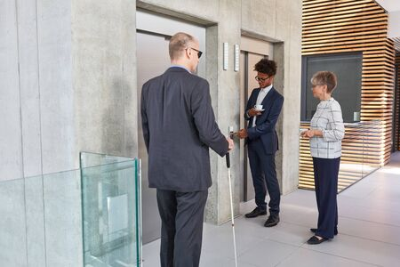 Business people and a blind man with a cane in front of an elevator in the office
