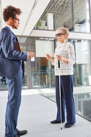 African businessman talking to a blind woman with a cane