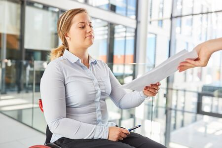 Businesswoman in a wheelchair with documents in the office for inclusion and career