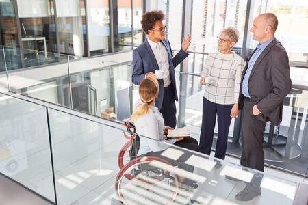 Multicultural business team with colleague in a wheelchair at a meeting Stock Photo