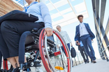 Workers and disabled woman in a wheelchair on a ramp in front of the office
