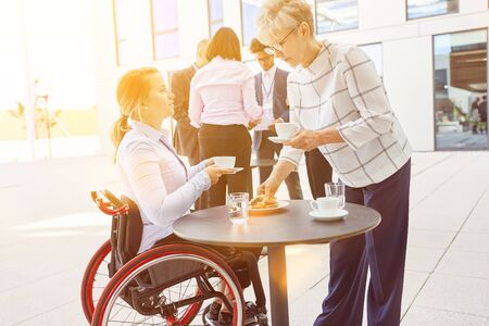 Businesswoman talks to woman in wheelchair during coffee break in front of the office