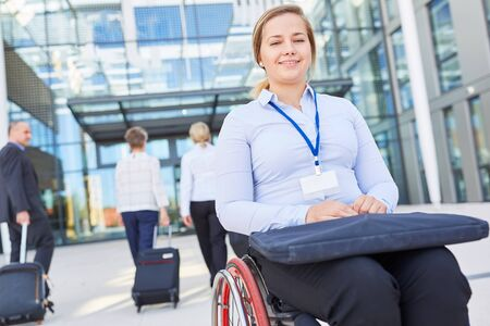 Disabled businesswoman in wheelchair on arrival to congress on inclusion Stock Photo