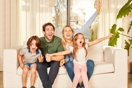 Les parents et les enfants applaudissent avec joie sur le canapé en tant que fans lors du match de football