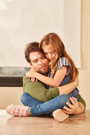 Unhappy father and daughter hold each other in their arms and comfort each other lovingly