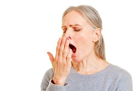 Fatigué femme plus âgée bâillant tenant sa main sur sa bouche Banque d'images