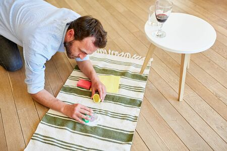 Man as a housewife removes with lemon and salt red wine stains from carpet