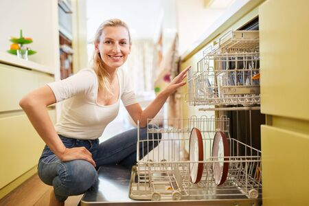 Young woman as a housewife putting in or removing the dishwasher