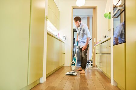 Hausmann cleans the parquet floor in the corridor with the steam cleaner