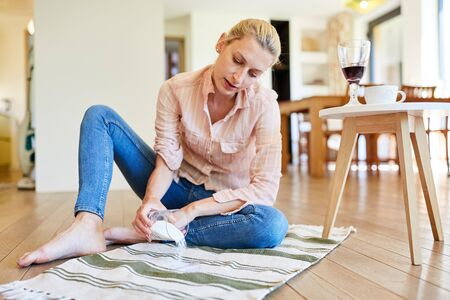 Housewife uses salt to remove red wine stains on a carpet