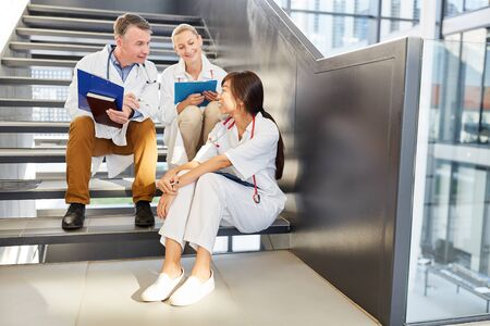 Young medical team in a break in the staircase of the clinic while relaxed small talk
