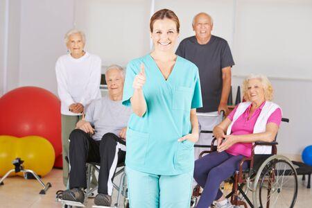 Verpleegkundige in verpleeghuis houdt duimen omhoog met een groep senioren Stockfoto