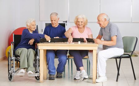 Group of seniors plays together Rummikub in the nursing home