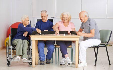 Grupo de personas mayores juega juntos Rummikub en el hogar de ancianos