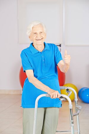 Old woman with physiotherapy walker keeps her thumbs up