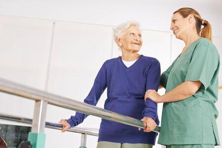 Stara kobieta z fizjoterapeutą podczas terapii ruchowej w domu opieki