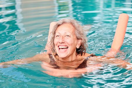 Active senior woman is having fun with aqua fitness in the pool with a buoyancy aid