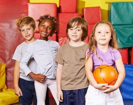 Glückliche Gruppe von Kindern steht mit einem Ball in der Vorschule