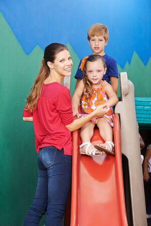 Young woman as a teacher beside children on a slide in kindergarten