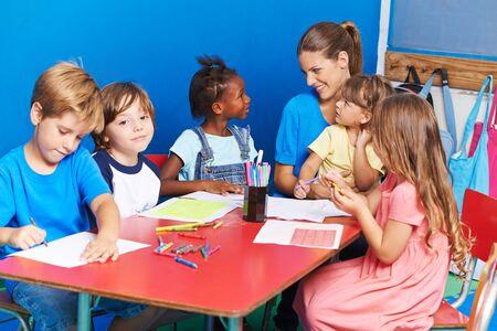 Grupo de contenido de niños mientras dibujan juntos en preescolar con el maestro