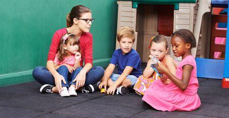 Los niños en el jardín de infantes miran un libro de imágenes con el educador