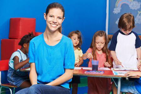 Lächelnde Erzieherin vor einer Gruppe von Kindern beim Malen im Kindergarten Standard-Bild