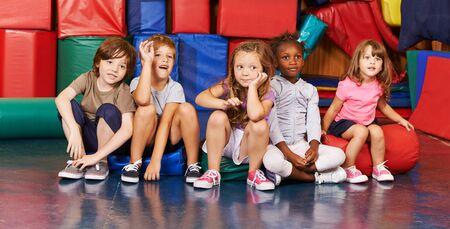 Groep kinderen zit gelukkig in de sportschool van een kleuterschool