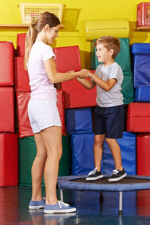 Laughing child hops on a trampoline in the gym from kindergarten