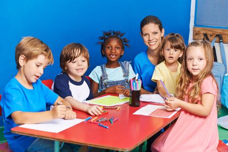 Many children draw together in kindergarten at the table with a teacher