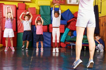 Joyeux groupe d'enfants ensemble pendant que les enfants font du sport à l'école maternelle