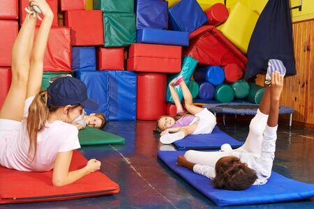 Children do gymnastics in kindergarten together with the teacher in the gym