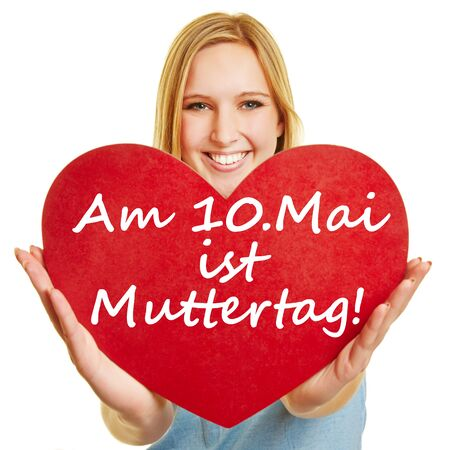 """Blond young woman holds red heart with the German text """"Am 10. Mai ist Muttertag!"""" (May 10th is Mother's Day!) Stock fotó"""
