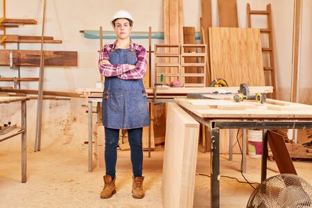 Young woman with safety helmet as a craftsman apprentice in joinery or joinery