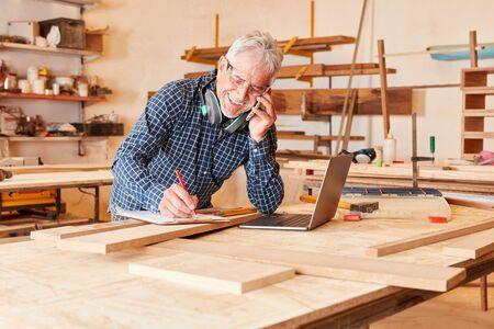 Alter Handwerker telefoniert in seiner Schreinerei