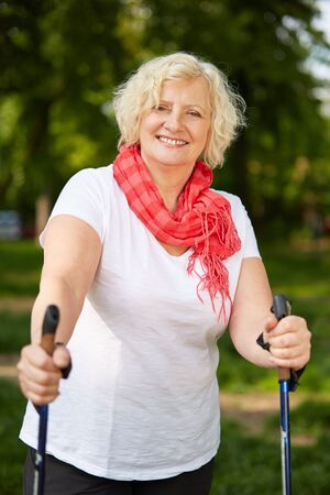 Elderly smiling woman is doing nordic walking in nature in summer