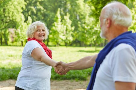 Happy couple of seniors while dancing in the garden in summer Stock Photo