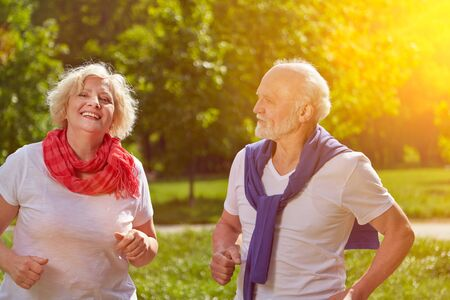 Happy couple of seniors running in the park in summer