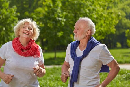 Two smiling seniors jog together in nature in summer