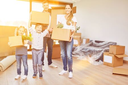 Happy family with two kids moving to home after buying a house Archivio Fotografico