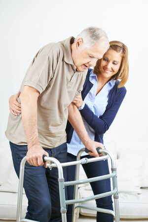 Nurse helps senior while walking with walker in retirement home