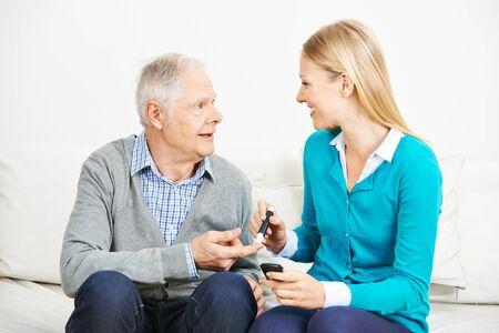 Młoda kobieta mierzy poziom cukru we krwi seniora chorego na cukrzycę w domu opieki