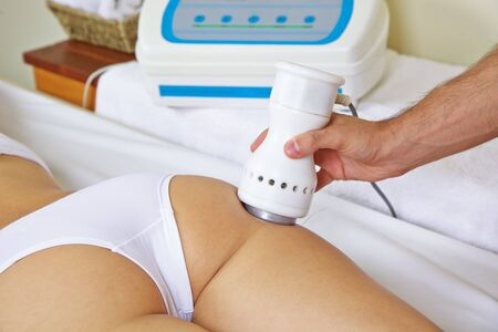 Woman gets electric massage on butt for skin tightening in the spa Stockfoto