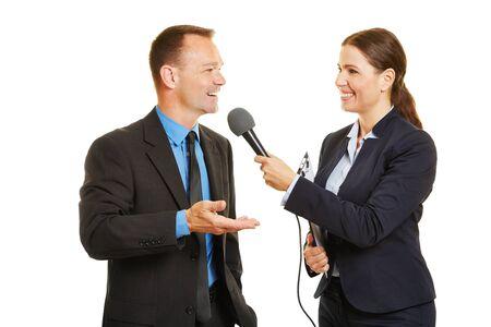 会社のプレススポークスマンは、マイクでジャーナリストにインタビューします