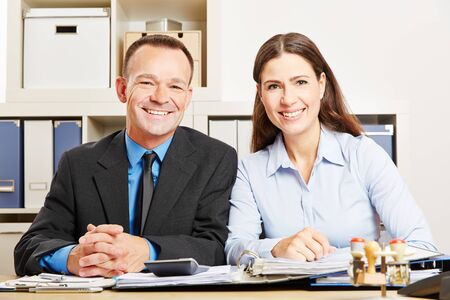 Man and woman are sitting together in the office at a desk