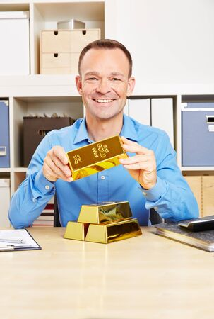 Smiling man holds gold bars in his hand at the desk in the office