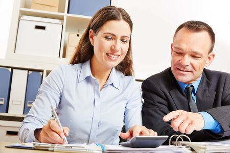 Office clerk beside manager pays out finance in the office 免版税图像