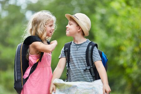 Two kids with backpack and hiking map together in summer vacations