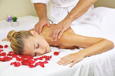 Young woman gets a relaxing massage for her back in the spa