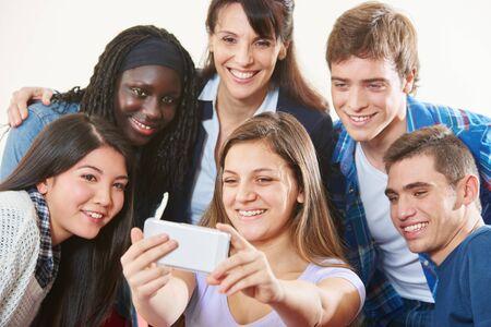 Lachende Schülergruppe macht zusammen ein Selfie mit Lehrer