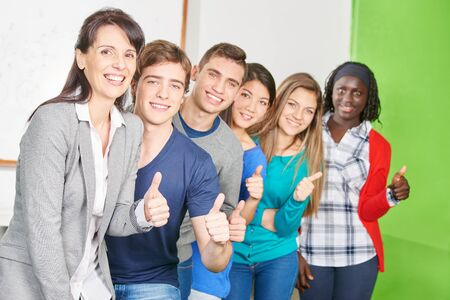 Successful student with teacher hold the thumbs up at school